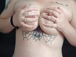 Tattooed girl plays with pierced boobies
